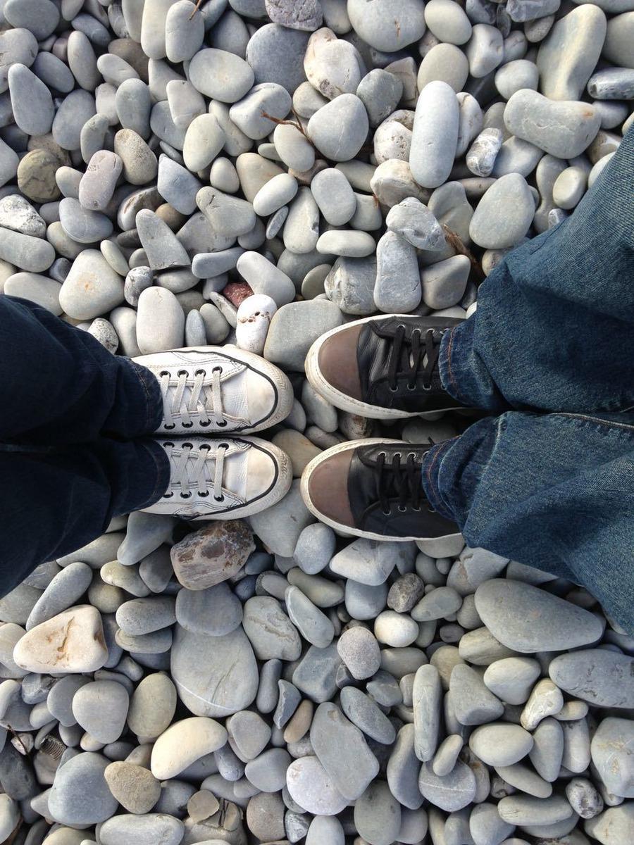 Pés vistos de cima em uma praia de pedras, ambiente externo