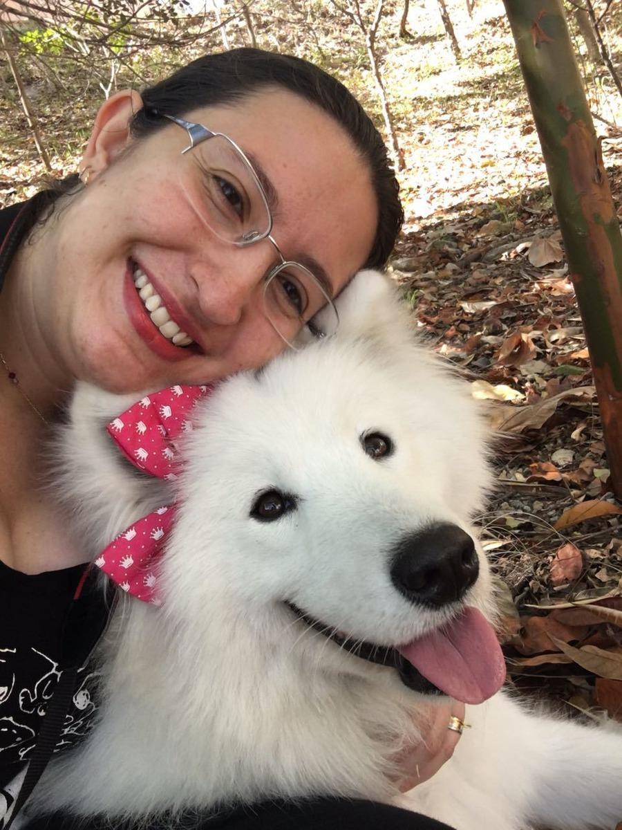 Selfie de uma mulher com um cachorro branco peludo de lacinho