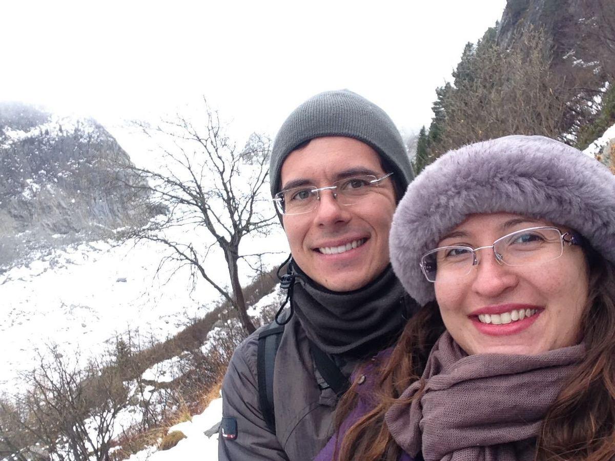 Selfie de duas pessoas em uma montanha com neve e árvores sem folha