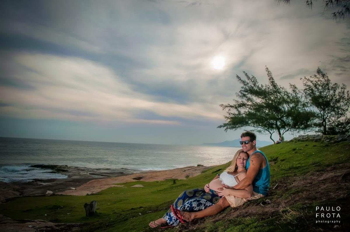 foto do casal deitado na grama da igreja, com horizonte ao fundo.