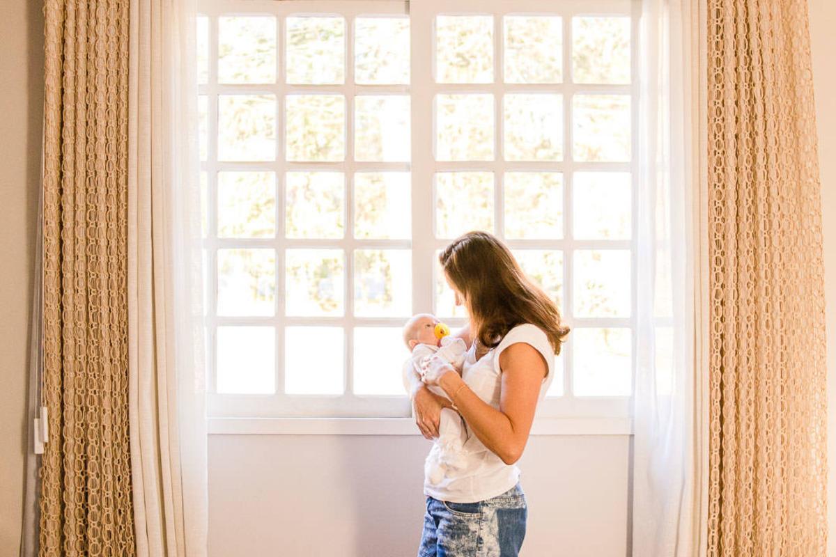 mãe com bebê recém nascido no colo e olhando para ele em frente a janela da casa