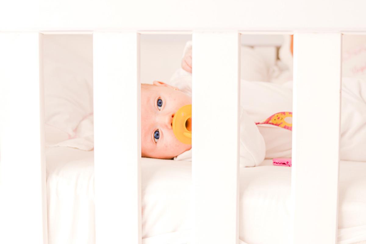 bebê recém nascido deitado no berço com chupeta na boca