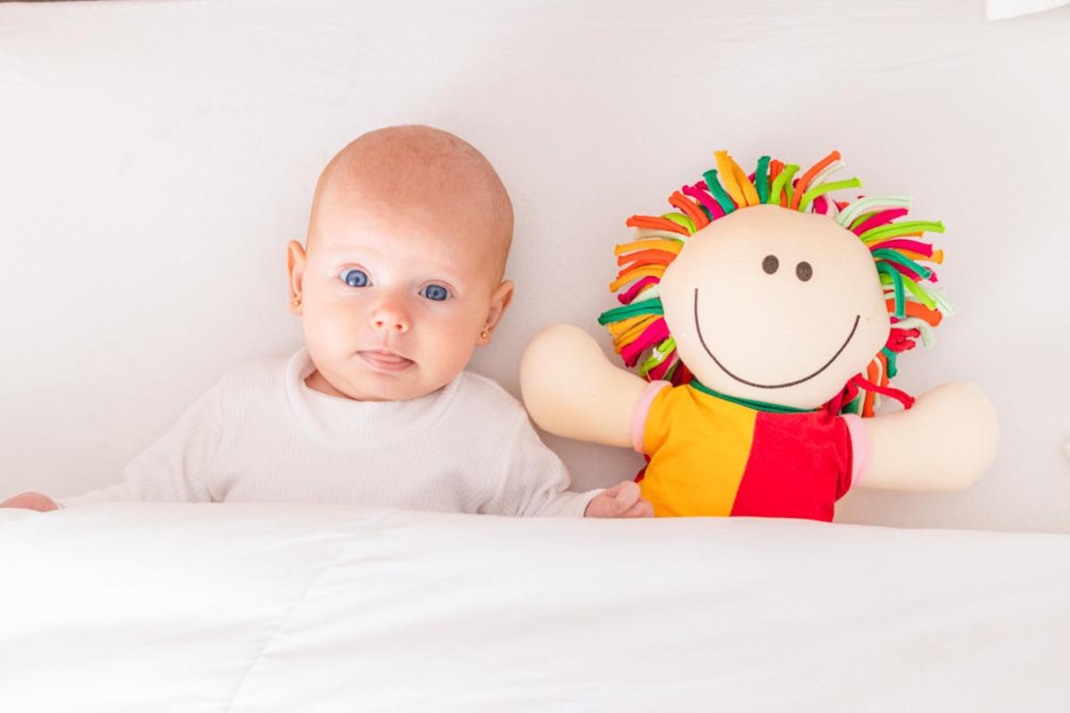 bebê recém nascido deitado com boneca olhando para a foto