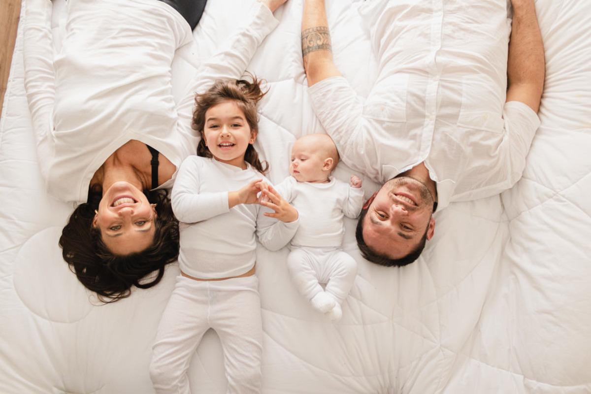 bebê recém nascido deitado com pai, mãe e irmã maior