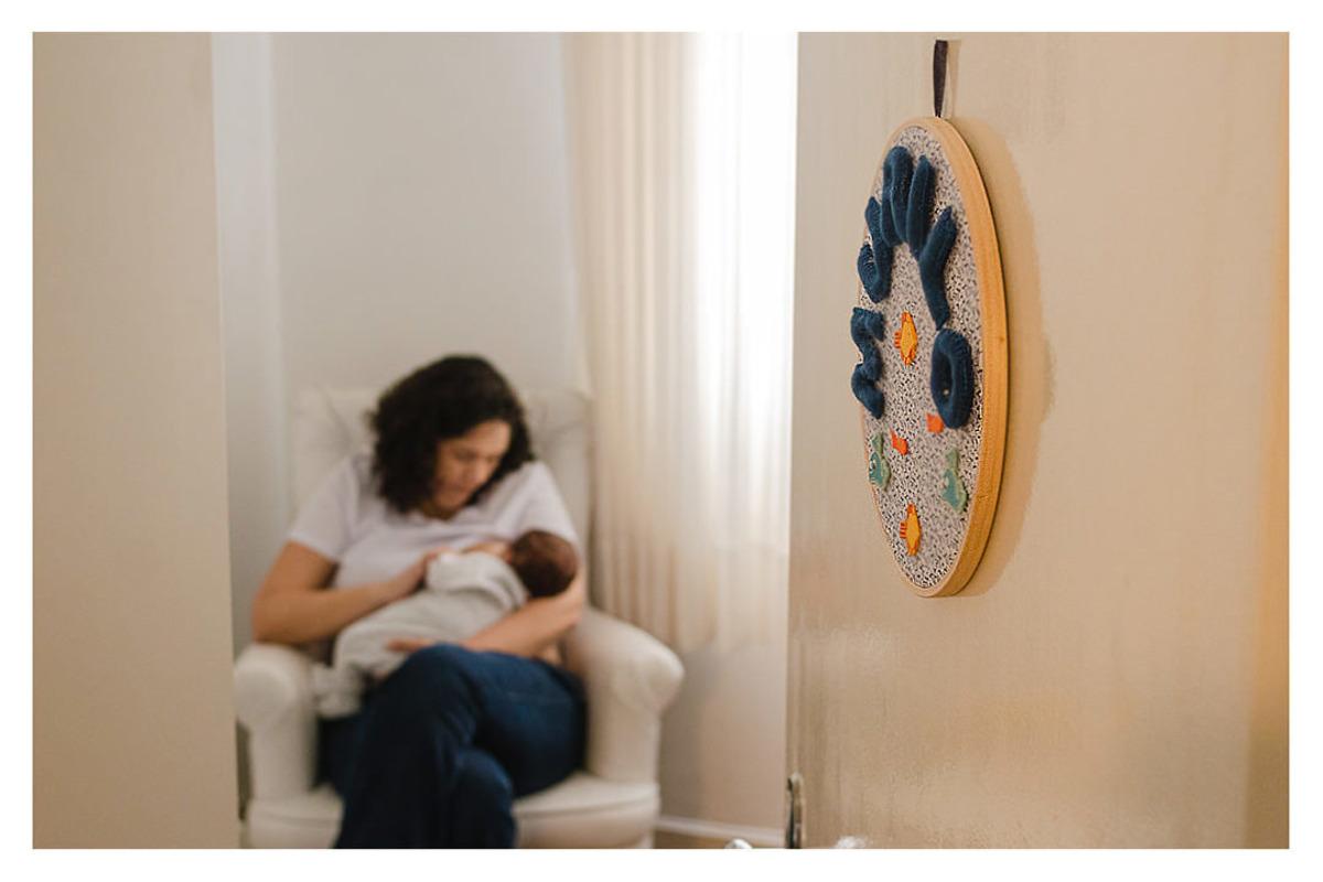 enfeite de quarto de bebê recém nascido mamando com mãe, durante a sessão de fotos de newborn lifestyle em Curitiba, do fotógrafo infantil e de família Rapha Luna