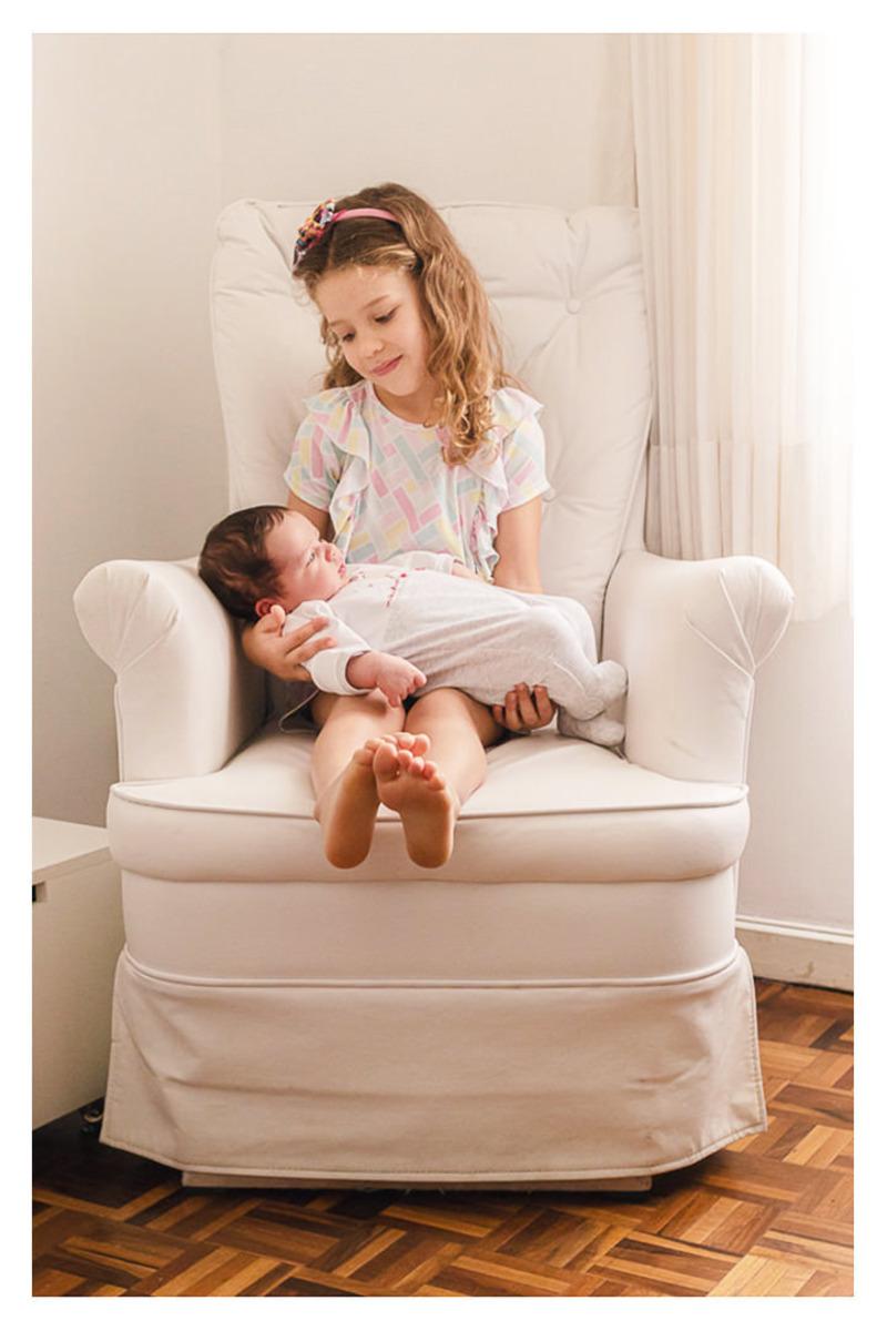 irmã sentada na poltrona de amamentação com bebê recém nascido no colo,  durante a sessão de fotos de newborn lifestyle em Curitiba, do fotógrafo infantil e de família Rapha Luna
