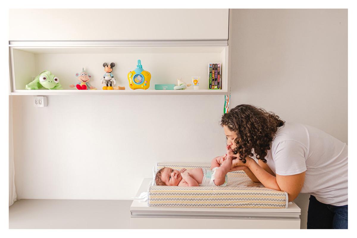 mãe brincando com os pés do bebê recém nascido deitado no trocador no quarto, durante a sessão de fotos de newborn lifestyle em Curitiba, do fotógrafo infantil e de família Rapha Luna