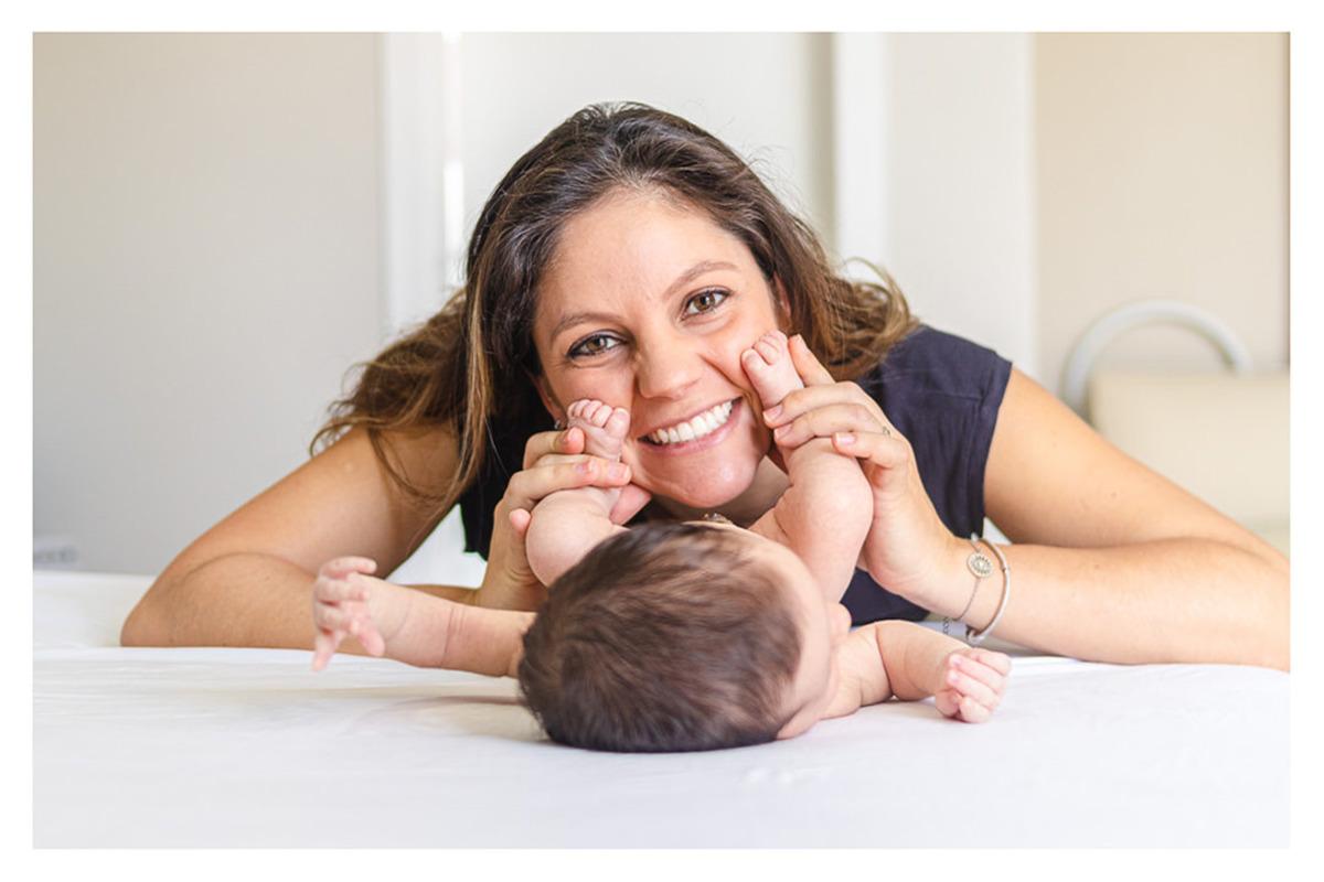 Mãe deitada na cama, sorrindo e brincando com os pés do bebê recém nascido,  durante a sessão de fotos de newborn lifestyle em Curitiba, do fotógrafo infantil e de família  Rapha Luna