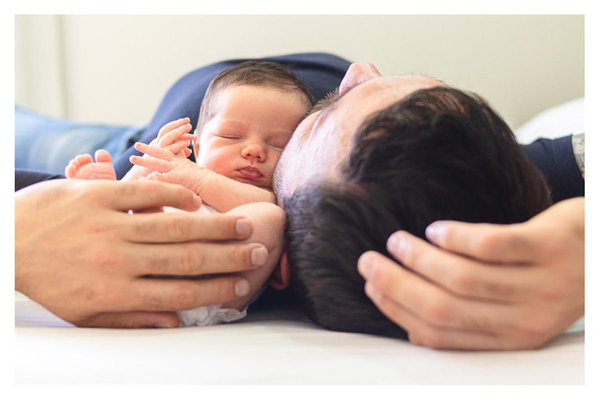 Bebê Newborn,  recém nascido, deitado na cama com o pai, durante a sessão de fotos de newborn lifestyle do fotógrafo infantil e de família  Rapha Luna de Curitiba