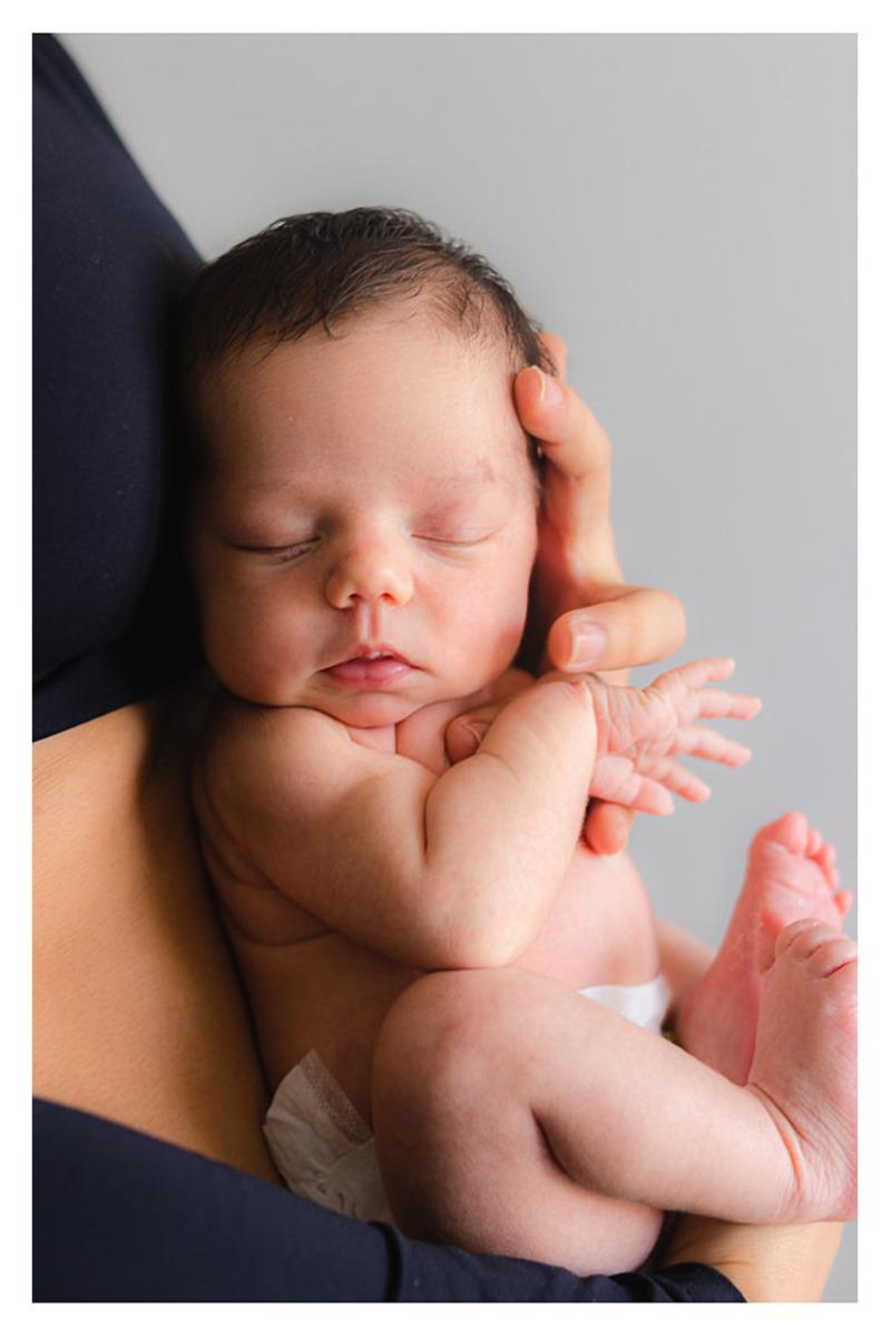 bebê recém nascida dormindo de olhos fechados no colo da mãe  durante a sessão de fotos de newborn lifestyle em Curitiba, do fotógrafo infantil e de família Rapha Luna