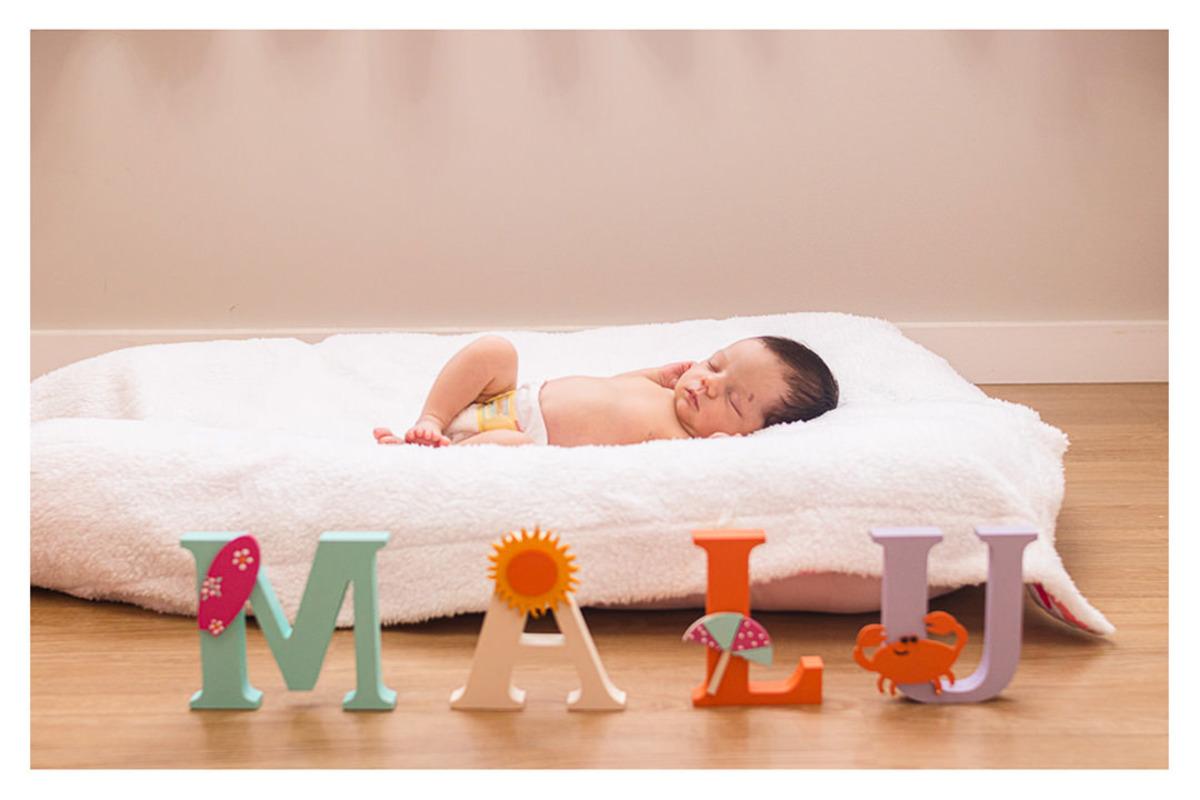bebê recém nascido deitado com objetos de decoração do quarto, durante a sessão de fotos de newborn lifestyle em Curitiba, do fotógrafo infantil e de família Rapha Luna