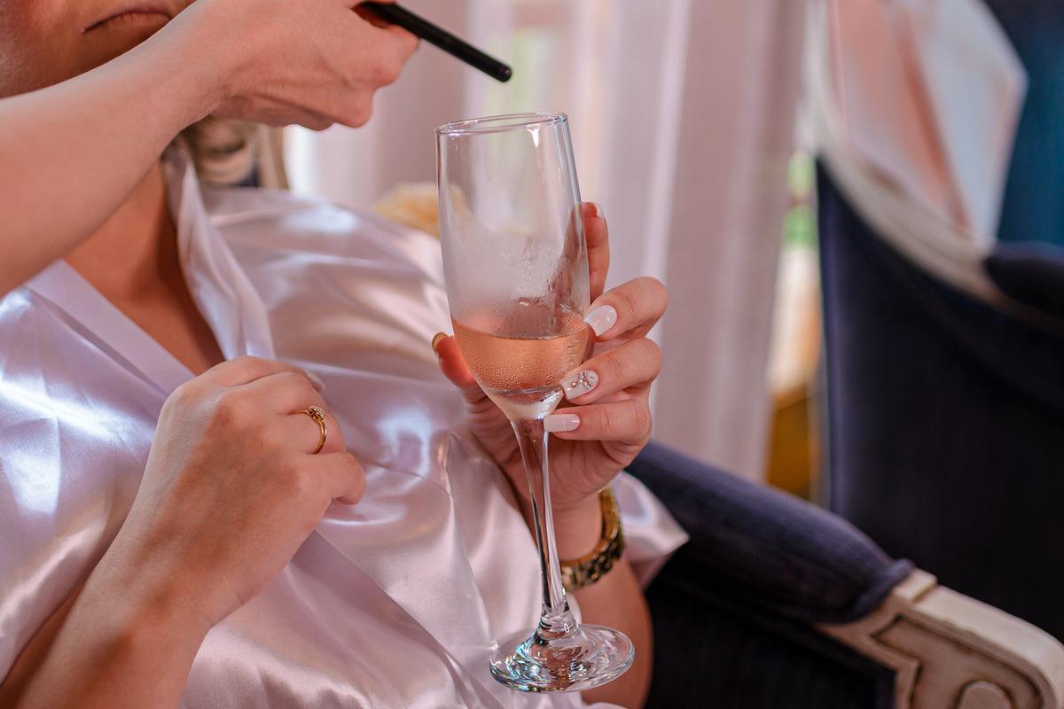 detalhes das unhas e da taça na mão da noiva