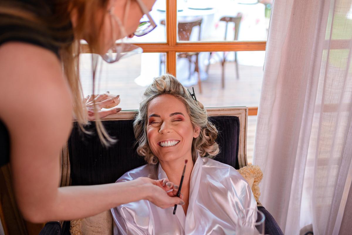 noiva sendo maquiada e rindo