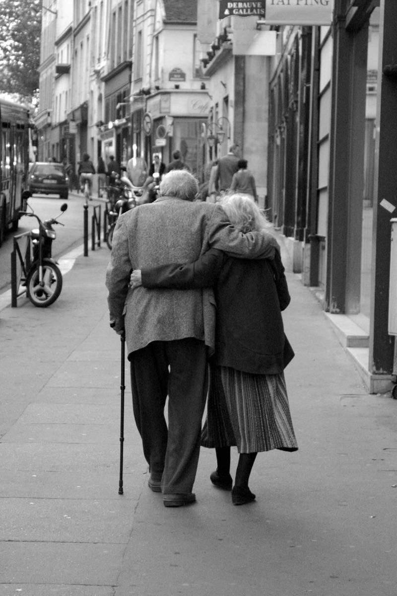 Casal de idosos caminhando abraçados na rua