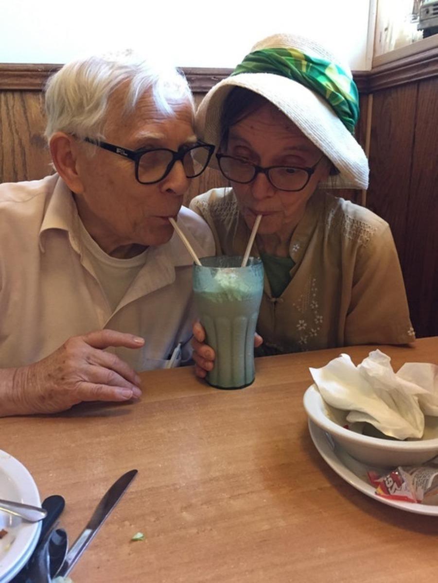 Casal de idosos tomando milk sheik no mesmo copo