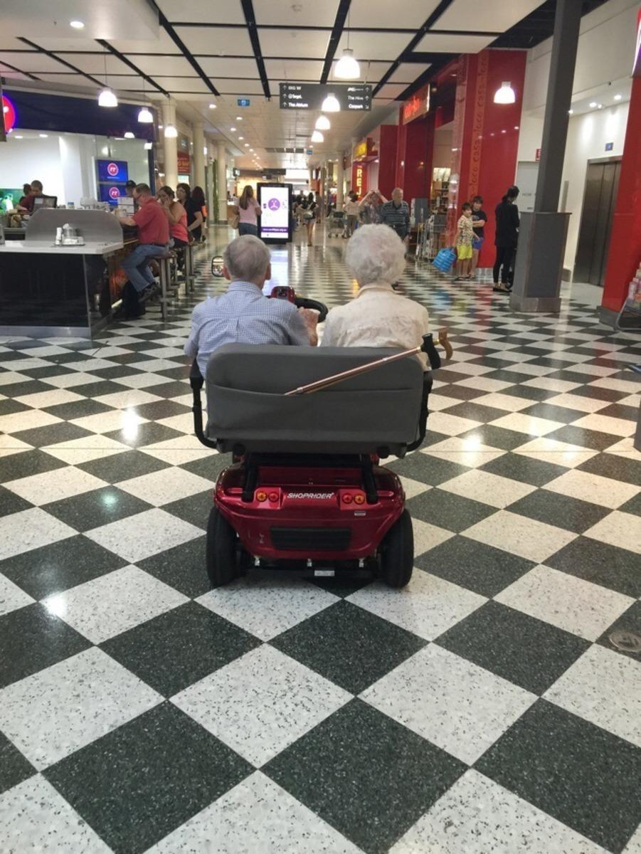 Casal de idosos em uma scooter para dois