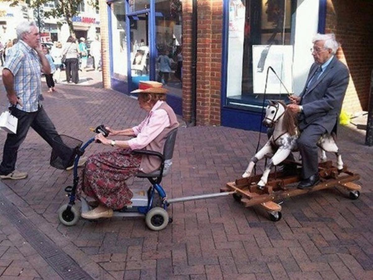 Esposa rebocando marido em seu triciclo