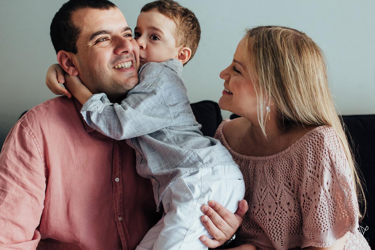 pai, mãe e filho se divertem em sessão fotográfica no sofá da sala