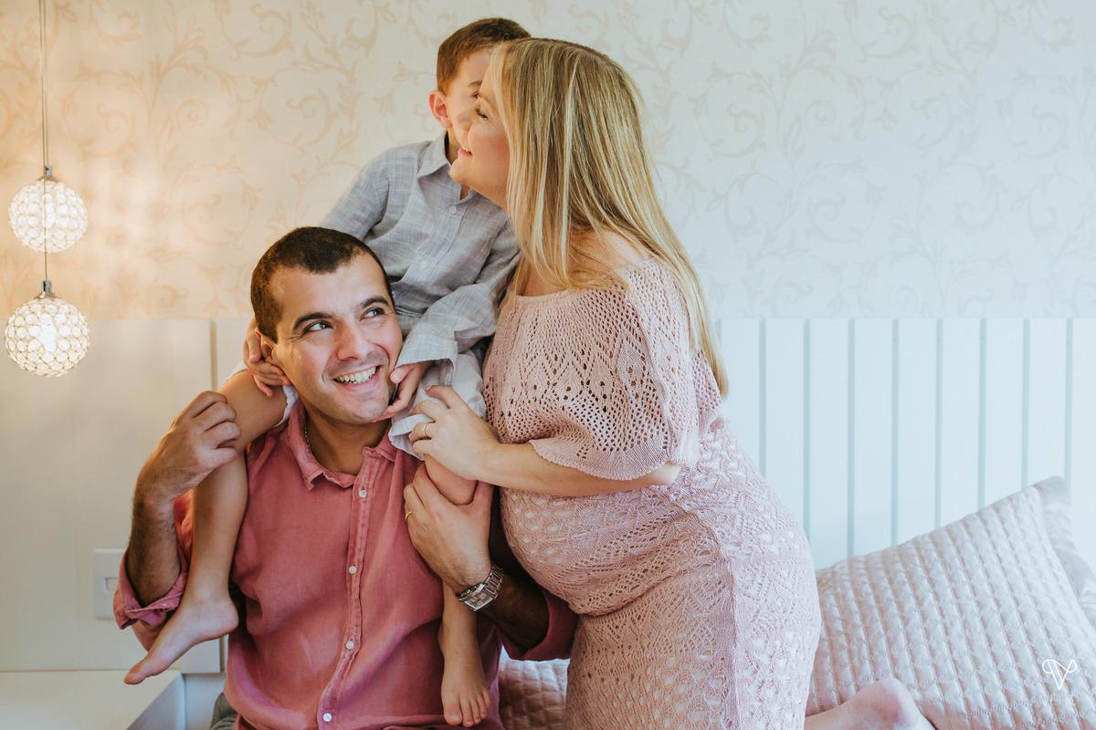Pai, Mãe e filho se reunem na cama. Criança beija os pais